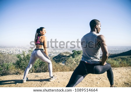 Couple of  joggers doing stretching before starting to run #1089514664