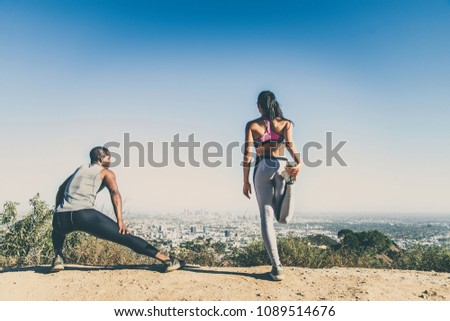 Couple of  joggers doing stretching before starting to run #1089514676