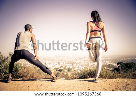 Couple of  joggers doing stretching before starting to run #1095267368