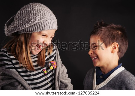 Couple of kids laughing on black background.