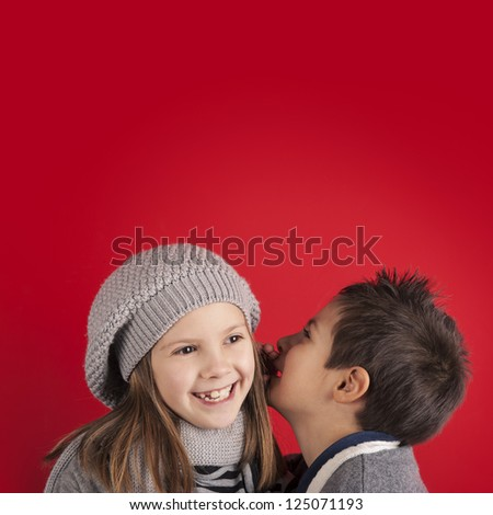 Couple of kids whispering on red background with copy space. Valentines day concept.