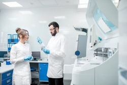 Couple of laboratory assistants in uniform working with test tubes standing near the analyzer machine in the laboratory
