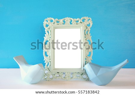 Couple of Lovebirds and blank photo frame on wooden table in front of blue pastel background. Ready to put photography