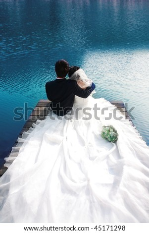 couple of lover sitting by lake