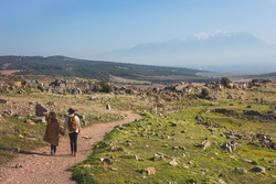 Couple of lovers are walking on road at sunset hand in hand through mountainous area on green mountain meadow with view of huge foggy misty mountains with snow capped peaks in distance in Hierapolis