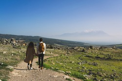 Couple of lovers are walking on road hand in hand through mountainous area on green mountain meadow with view of huge foggy misty mountains with snow capped peaks in distance in Hierapolis