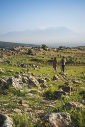 Couple of lovers are walking on road hand in hand through mountainous area on green mountain meadow with view of huge foggy misty mountains with snow capped peaks in distance in Hierapolis. Vertical