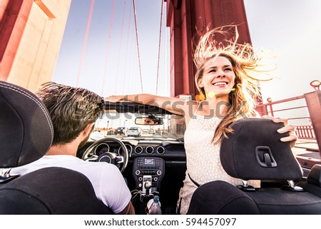 Couple of lovers driving on a convertible car - Newlywed pair on a romantic date, woman with outstretched arms on Golden Gate Bridge #594457097