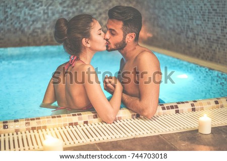 Couple of lovers kissing in spa swimming pool - Romantic love story on vacation resort hotel - Relationship concept with boyfriend and girlfriend together - Focus on woman eye - Warm contrast filter