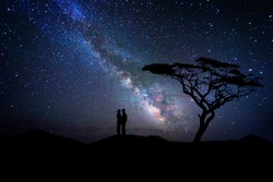 Couple of lovers silhouette kissing near a tree under the milky way