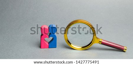 Couple of lovers standing near a magnifying glass. The concept of finding love and dating through the Internet. Search for the second half. Social networks and dating sites. Find your soul mate #1427775491