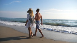 Couple of lovers walking at coast holding hands during resting on resort. Man and woman strolling on beach and enjoying summer vacation together. Honeymoon of young pair. Concept of love and happiness