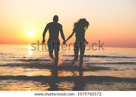 Couple of lovers walking inside water on tropical beach in summer vacation at sunset - Young people enjoying holidays - Love, travel and landscape concept - Focus on silhouettes #1079760572