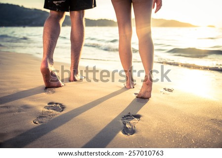 Couple of lovers walking on the each at sunset - Foot prints on the beach