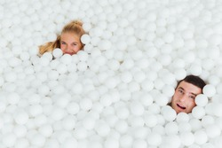 couple of loving friends have fun surrounded by white plastic balls in a dry swimming pool. Happy active date. Copy space.