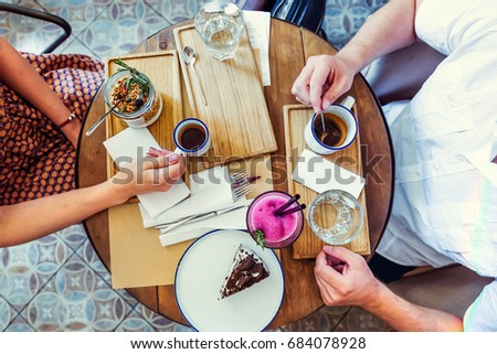 Couple of Man and woman on date having breakfast in the morning in cafe. Granola, chocolate cake, smoothie and hot coffee on the table. Flatlay, selective focus. #684078928