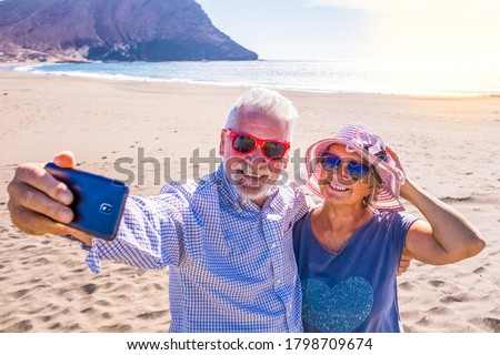 couple of mature people or pensioners enjoying their vacations and summer time together on the sand of the beach with the sea or ocean at the background - two retired senior taking a selfie smiling Foto stock ©