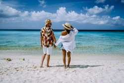 couple of men and woman mid age on the beach of Curacao, Grote Knip beach Curacao Dutch Antilles Caribbean. on a tropcial beach with white sand