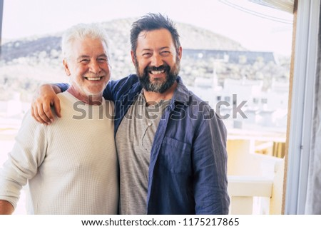 couple of men hugging and stay together in friendship and relationship. father and son different ages smi.ing and look at the camera. portrait of cheerful caucasian people mixed generations enjoy life #1175217865