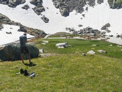 Couple of middle age hikers resting at alpine mountain meadow called Paradies with lush green grass and flowers. Stubai hiking trail, Summer Tyrol Alps, Austria