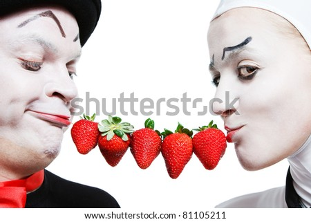 Couple of mimes taking the chain made of strawberries in the mouth and smiling on a white background