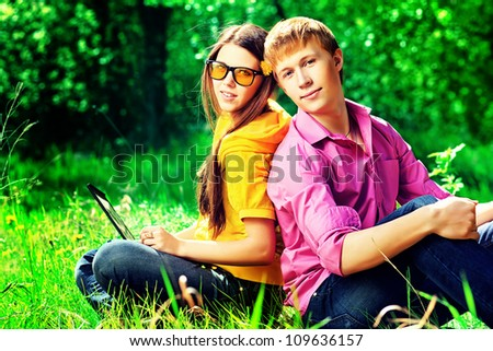 Couple of modern teenagers sitting with a laptop outdoors.
