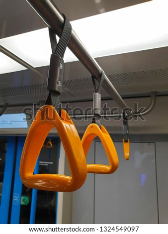 couple of new orange plastic handles in subway, bus or train with bright light and door in the background, safety handle for passengers
