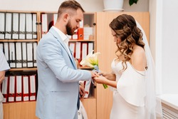 couple of newlyweds in the civil registry office. obtaining an official marriage certificate. A wedding for two. Groom in a blue suit and bride in an elegant white dress with a bouquet of calla.