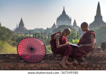 Couple of novice read a book on monastery\'s wall with field of ancient pagoda background in Old Bagan Myanmar