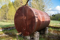 Couple of old rusty abandoned disel tanks in the forest. Text translation