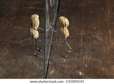 Couple of Peanut People being kept apart by a glass wall