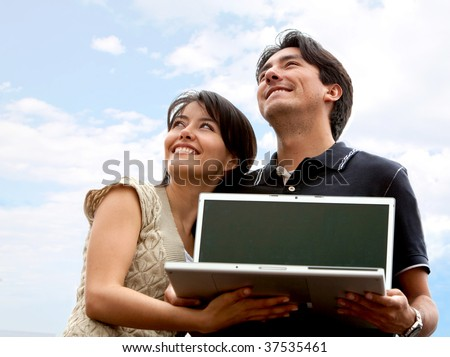 Couple of people with laptop outdoors