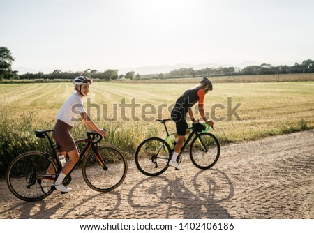 Photo of couple of pretty fit female and strong fast male at afternoon ride on bicycles, cross country, gravel. outstanding image of cyclist riding at warm summer day in Spain, Europe.  place for text.