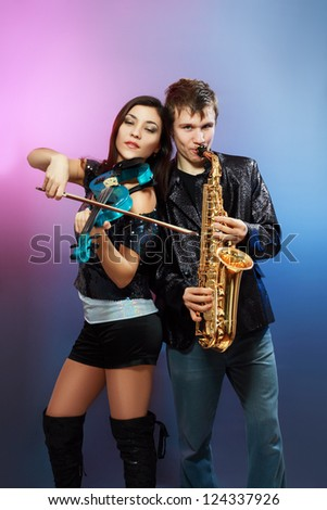 Couple of professional musicians in modern style posing in costumes at studio