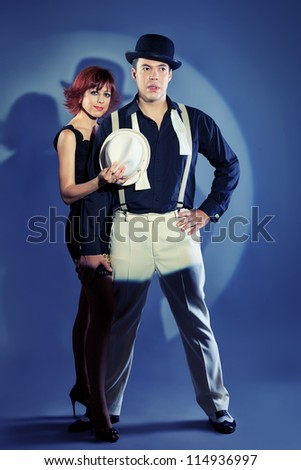 Couple of professional singers in retro style posing in costumes at studio.