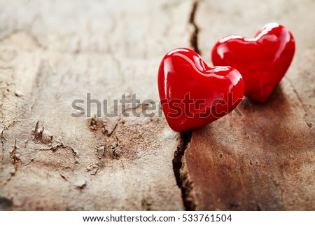 Couple of red hearts on rough cracked wood signifying love, romance and a special relationship with copy space for your Valentines greeting or message to a loved one