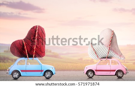 Couple of retro toy cars delivering craft hearts for Valentine's day against blurred sunset rural landscape