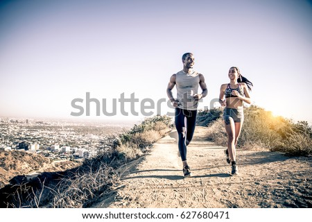 Couple of runners training outdoors - Two sportive people running #627680471