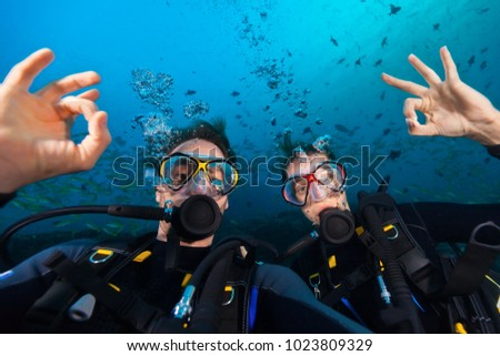 Couple of scuba divers showing ok sign, portrait photography. Underwater sports and activities #1023809329