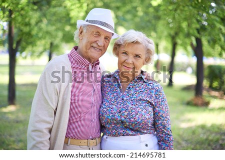 Couple of senior man and woman looking at camera in the park at summer