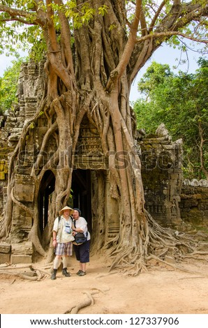 Couple of senior tourists in Ta Som temple, Angkor, Cambodia
