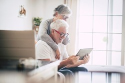 couple of seniors smiling and looking at the same tablet hugged on the sofa - indoor, at home concept - caucasians mature and retired man and woman using technology - lockdown and quarantine lifestyle
