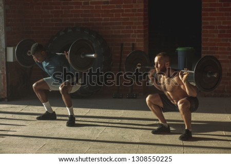 Couple of shirtless interracial male athletes pumping muscles with heavy weight barbell at indoor crossfit studio