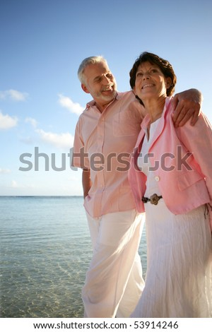 Couple of smiling seniors having a walk by the edge of the sea