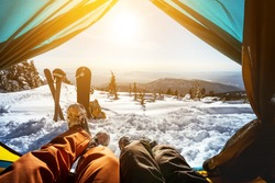 Couple of snowboarder and skier having rest in tent on the top of mountain