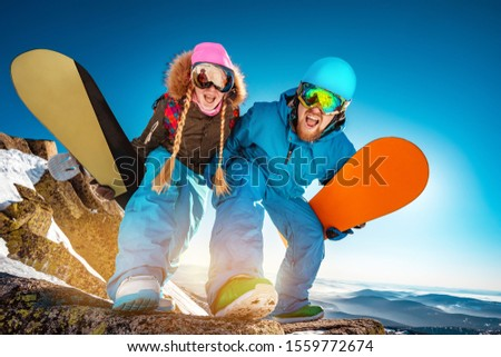 Couple of snowboarders male and female are having fun and posing for photo with snowboards #1559772674