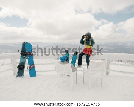 Couple of Snowboarders  seating on view point enjoy winter landscape in ski resort. Two snowboards standing near  #1572154735