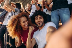 Couple of spectators taking selfie while cheering their sports team from a stadium. Cheerful man and woman fans taking selfie while watching match in stadium.