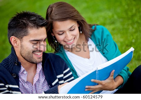 Couple of students holding a notebook outdoors and smiling