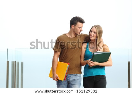 Couple of students walking towards camera outdoor with a white background